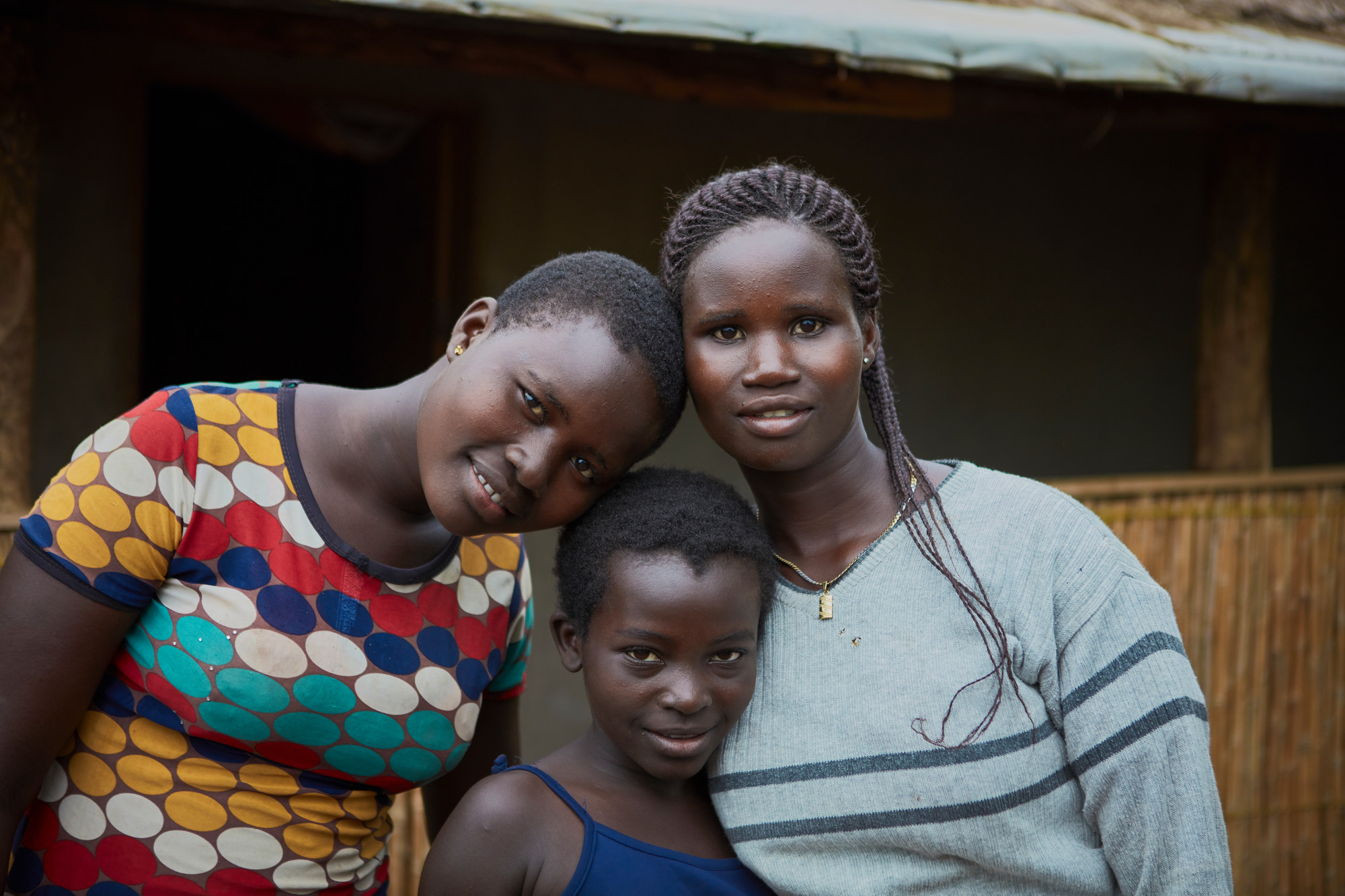 Three adolescent girls embrace while standing outside of a shelter in a refugee.