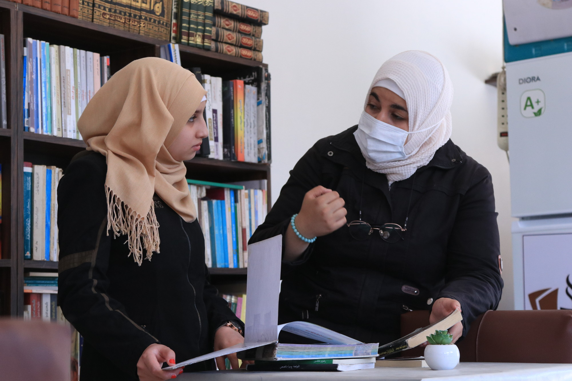 A woman in a face mask speaks with a girl in a library.