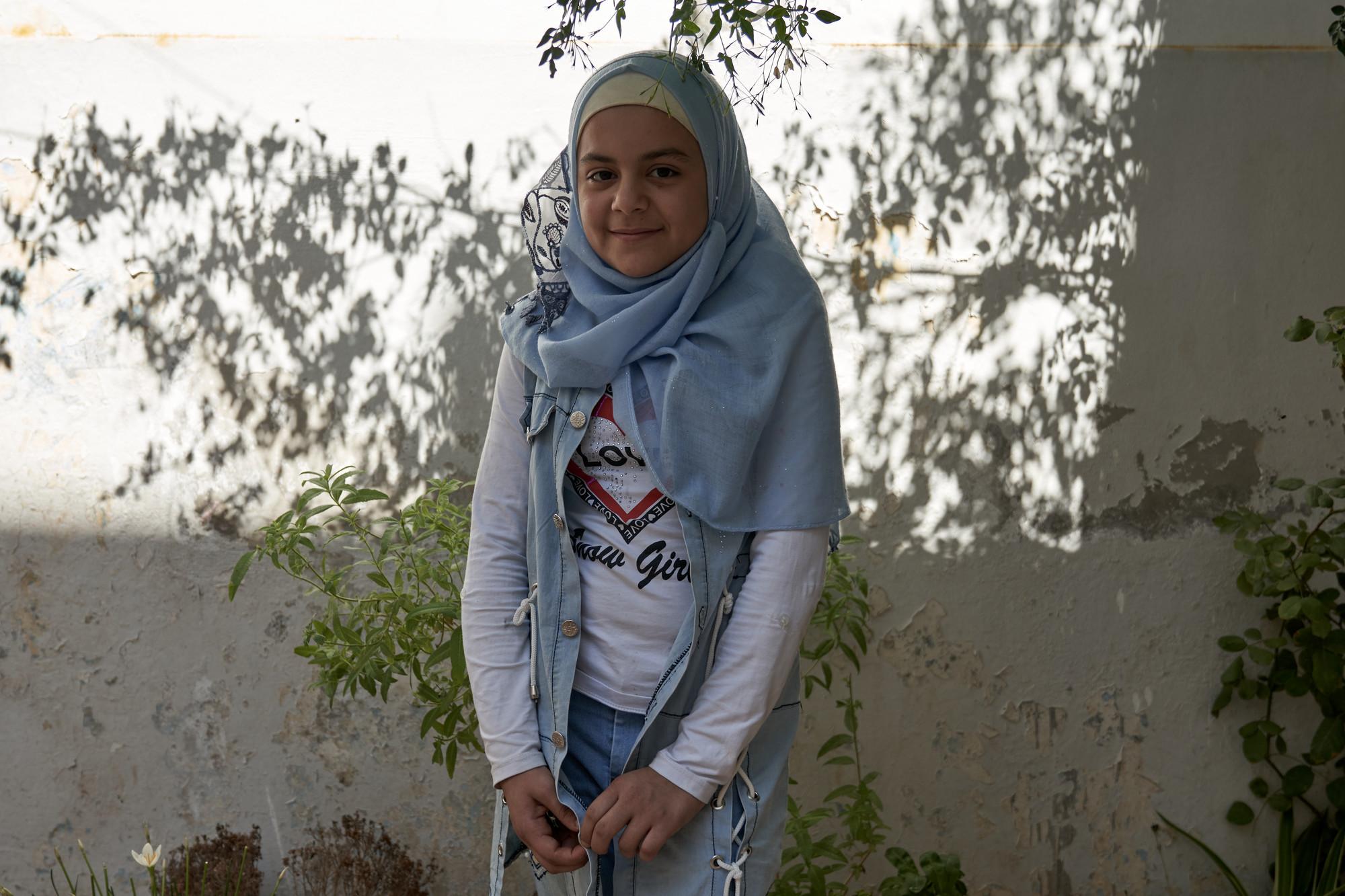 Una niña sonríe mientras está de pie frente a una casa.