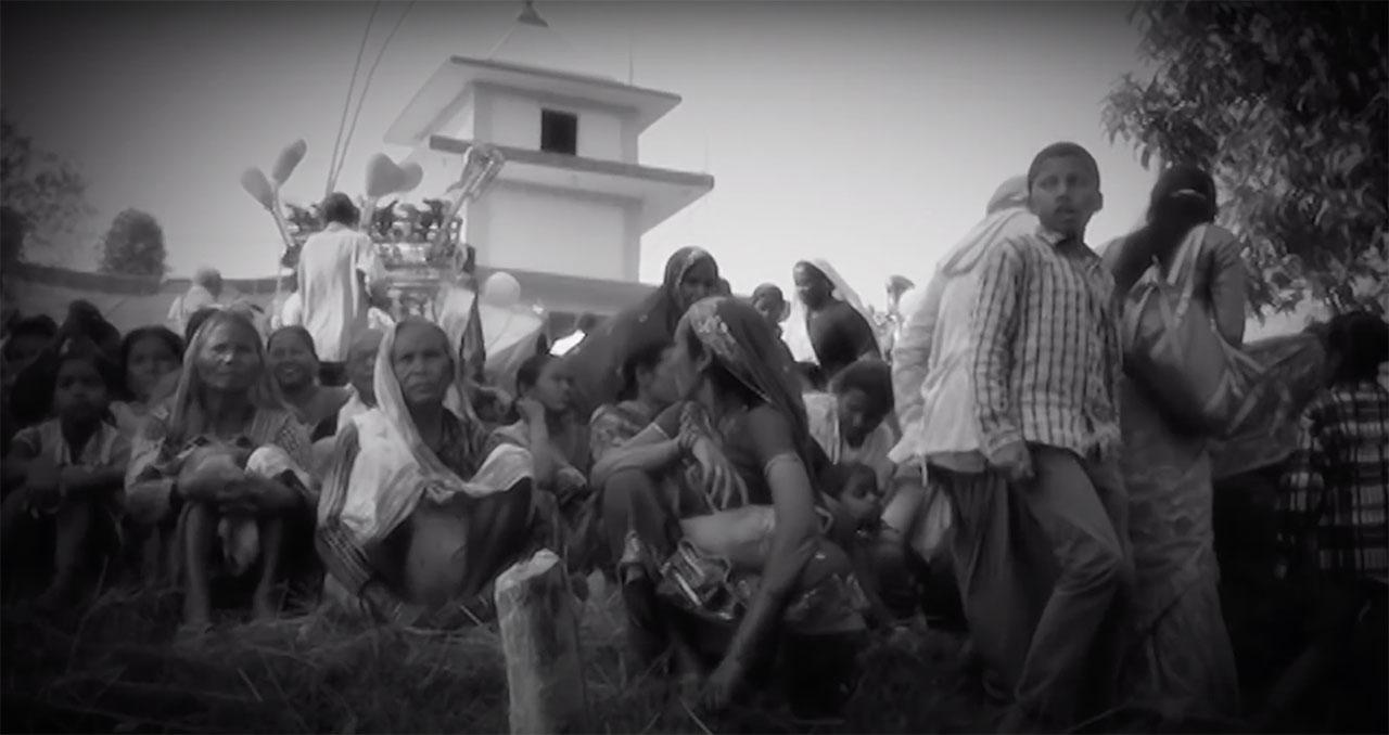 Uma imagem em preto e branco de um grande grupo de pessoas sentadas em frente a um edifício. No lado direito, um menino está de pé.