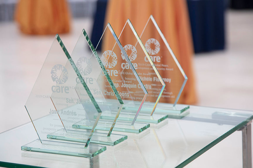 A close-up image of the CARE Global Leader Awards, which are all glass with white lettering.