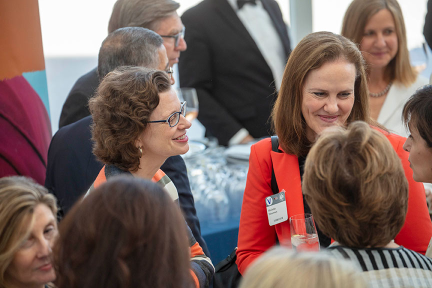 Michele Flournoy, wearing a bright red suit jacket, and Michelle Nunn, wearing an orange, gray, and white striped sweater, talk with attendees.