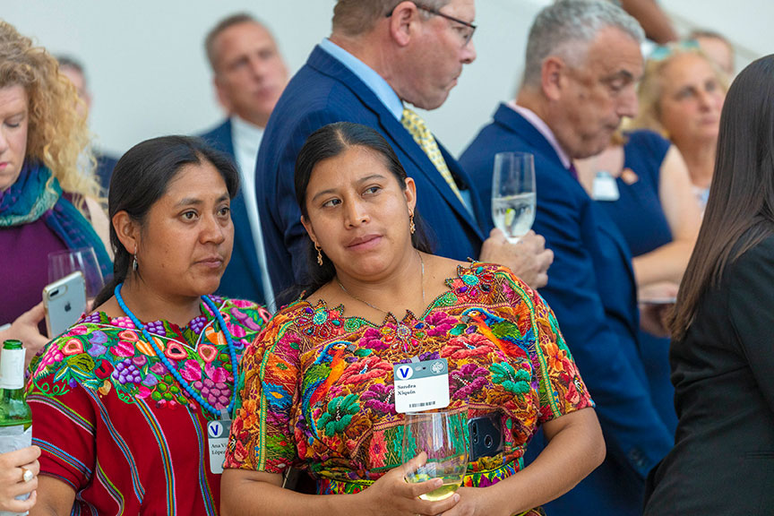 Two women wearing brightly patterned, embroidered outfits, talk.