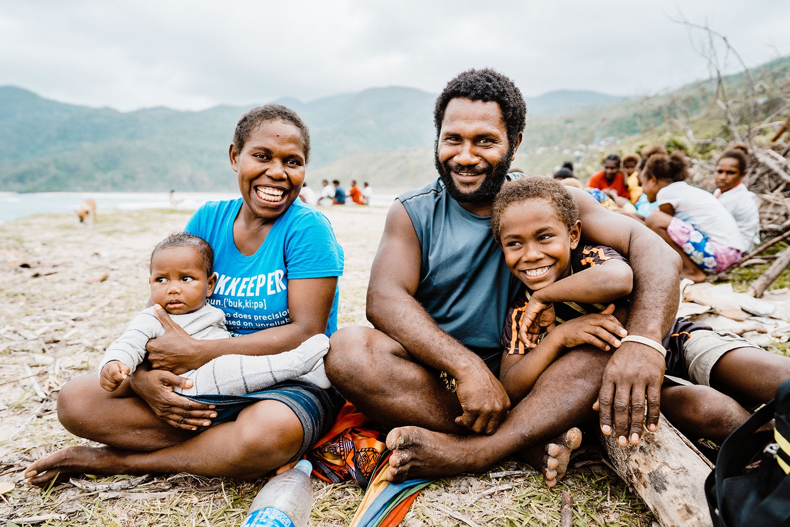 A family smiles while sitting on a beach