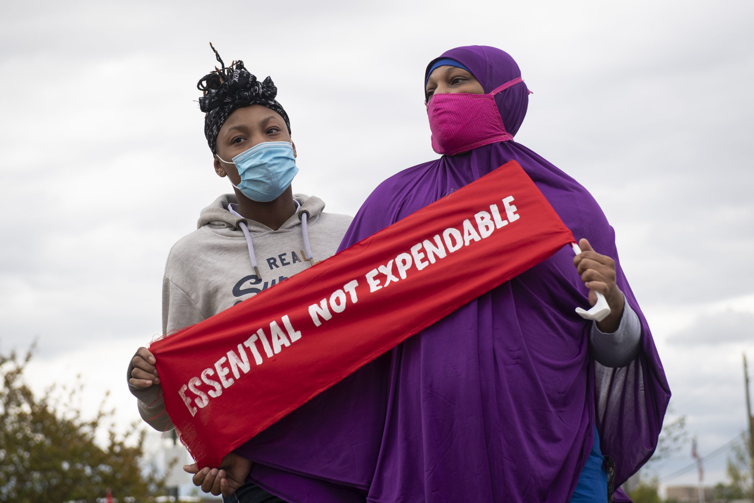 Two women in face masks hold up a sign that read