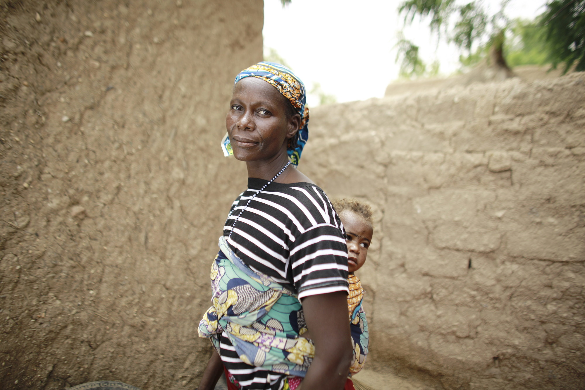 A woman with a child on her back stands outside in front of a wall