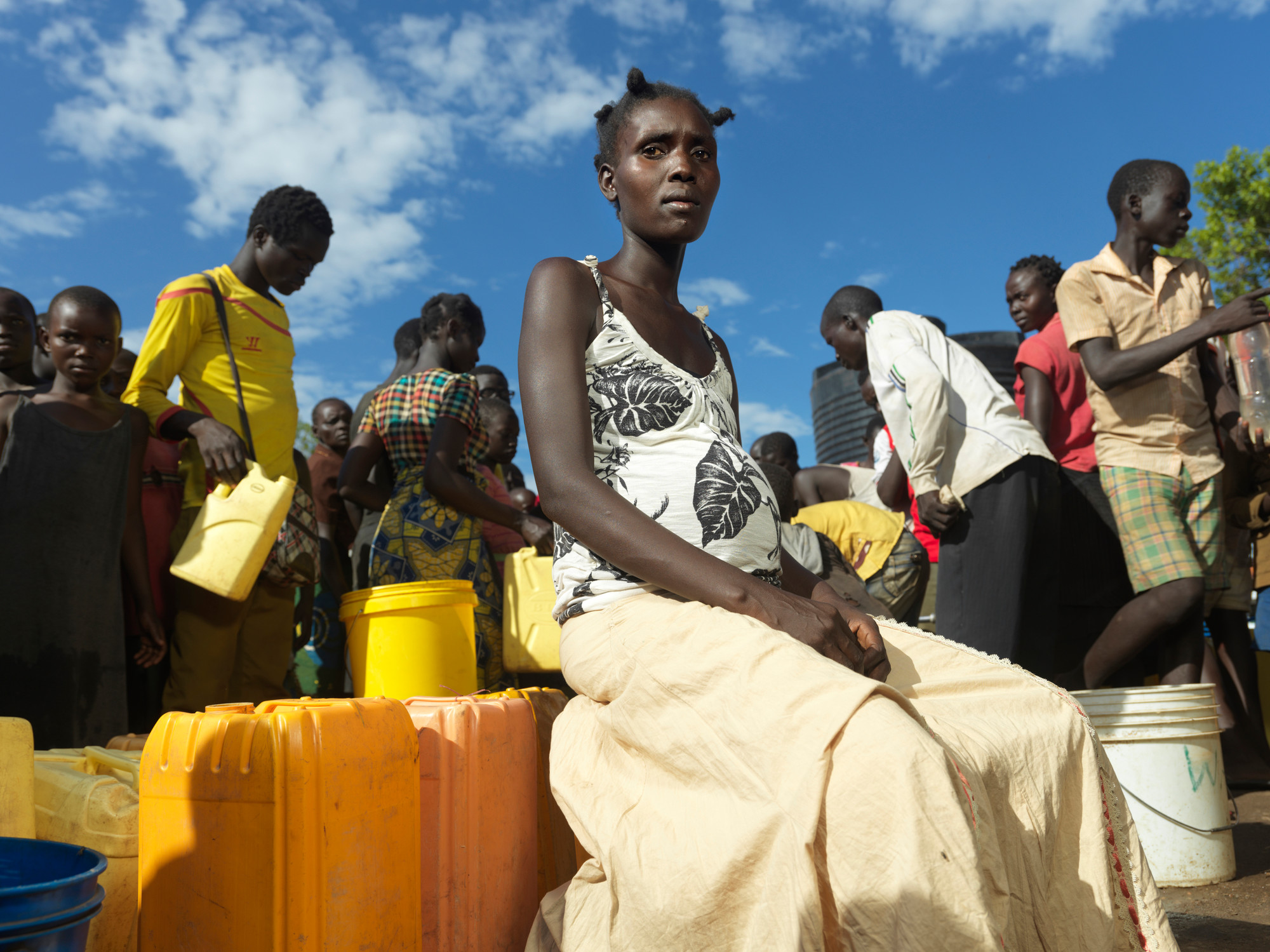 A woman sits on jerry cans in a crowd of people