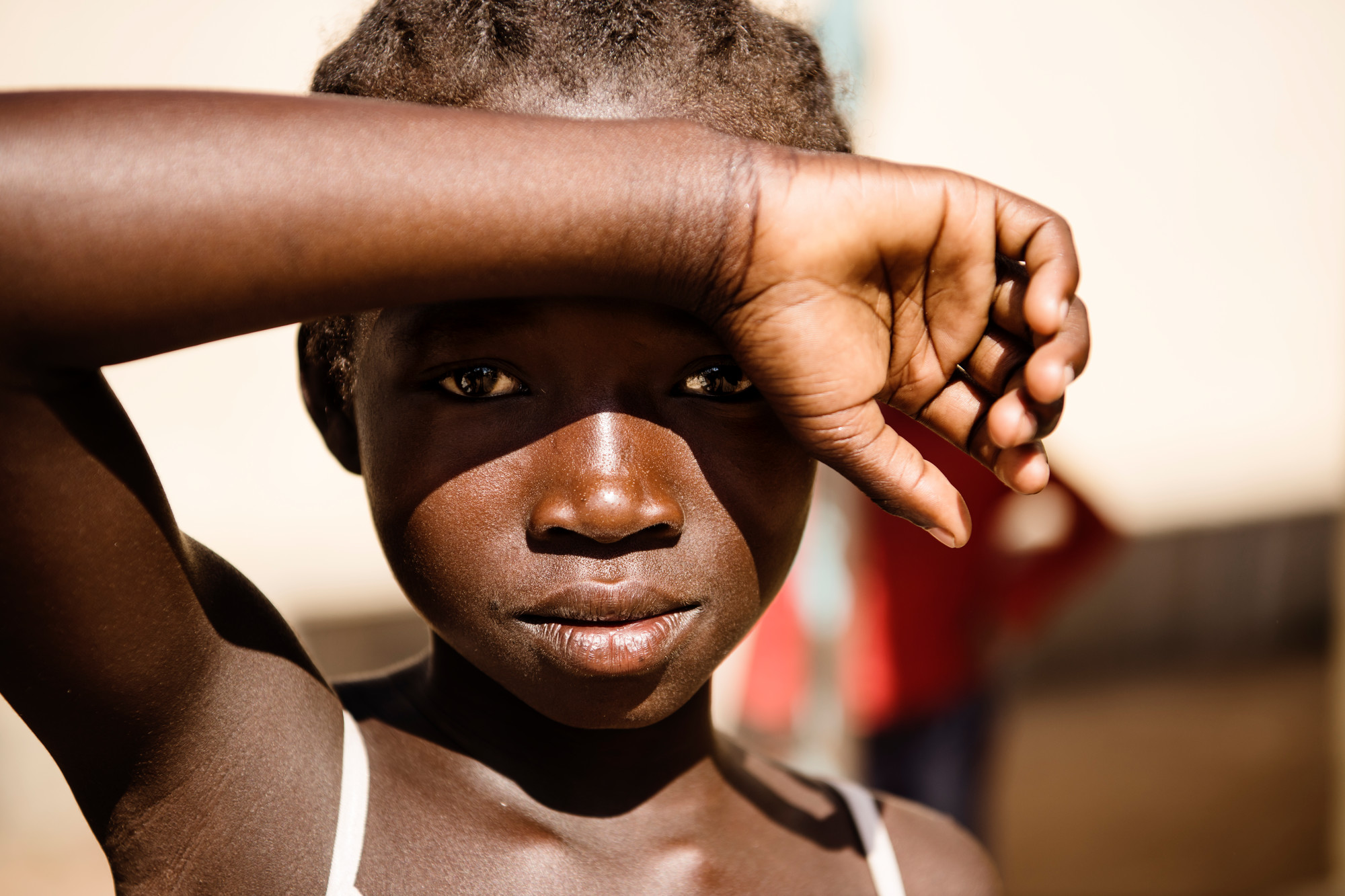 A girl shields her eyes from the sun with her arm over her brow.
