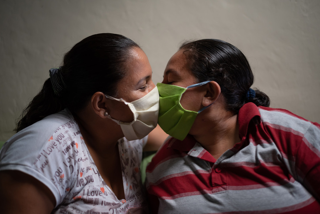 Two people kiss with face masks on