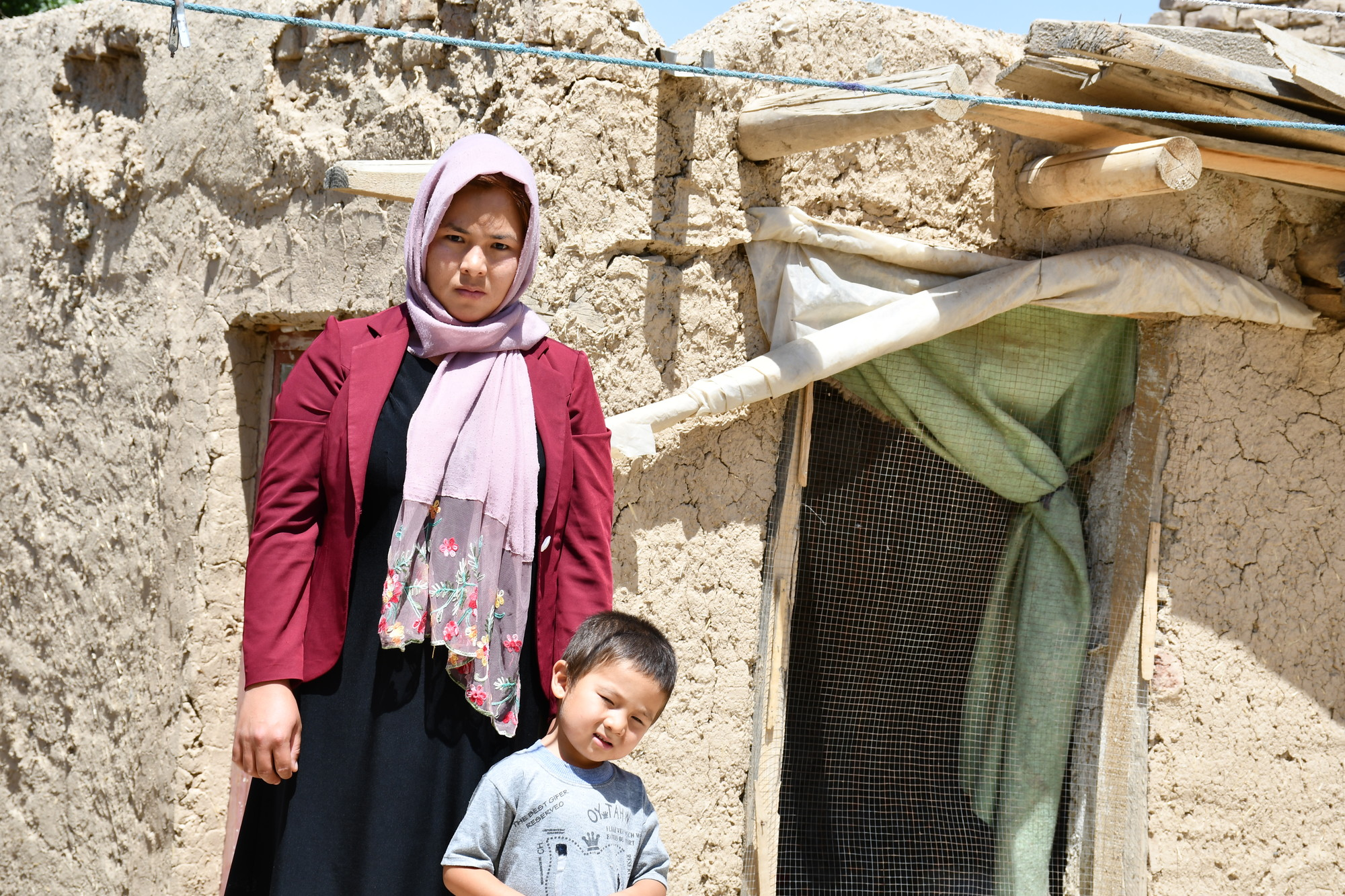 A woman and a small boy stand outside of a clay and wood home.