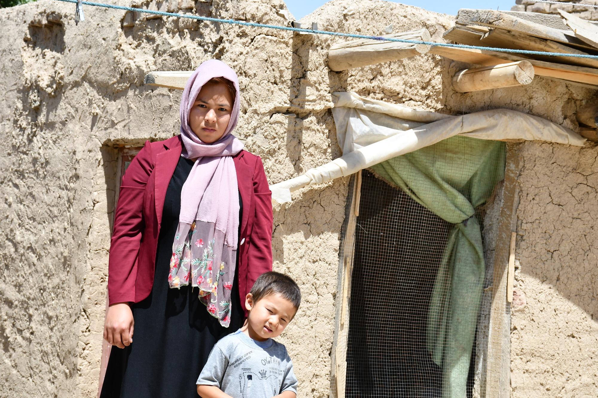 Uma mulher e um menino estão do lado de fora de uma casa de barro e madeira.