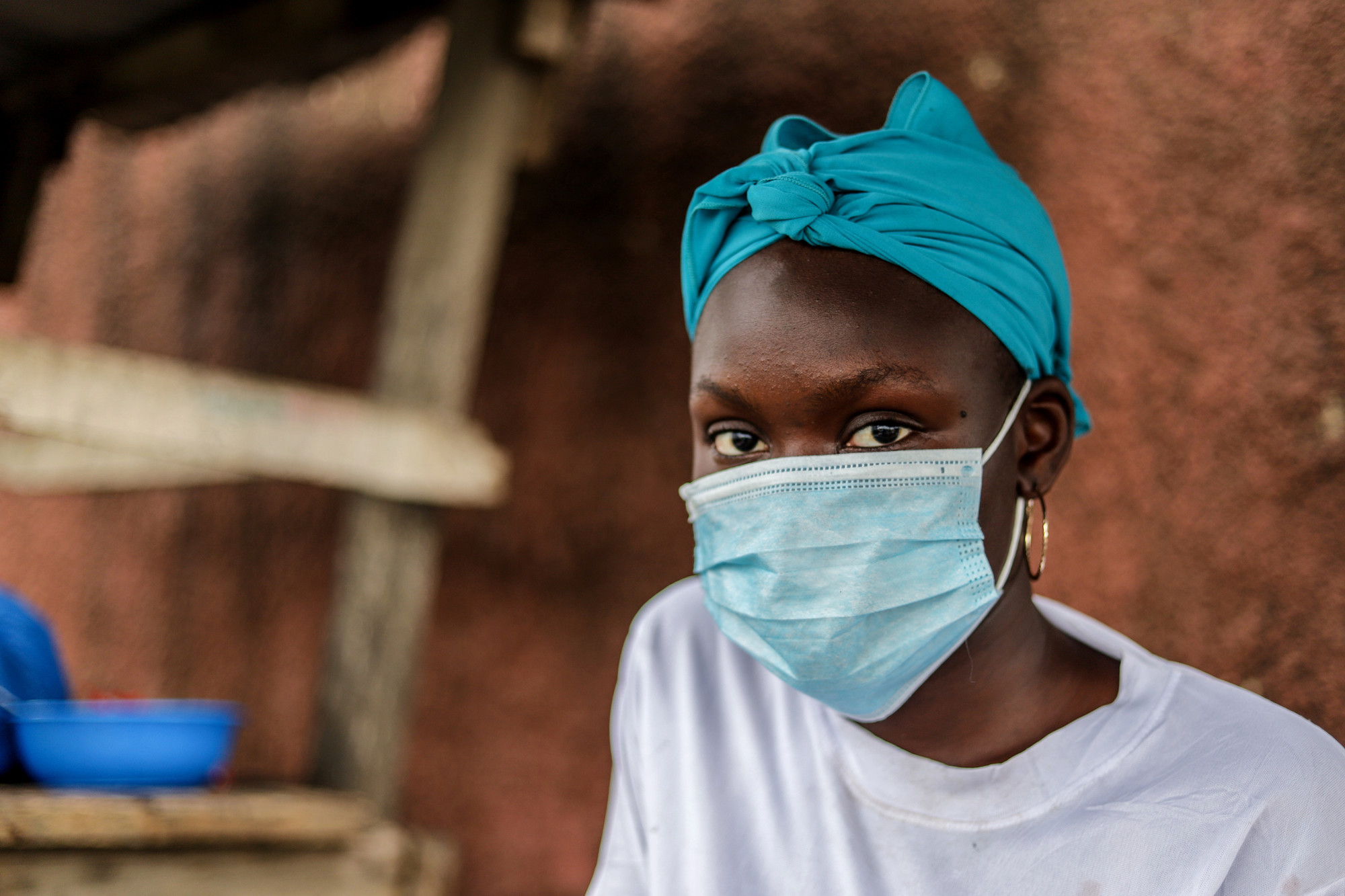 a woman wears a medical face mask in front of a clay building.
