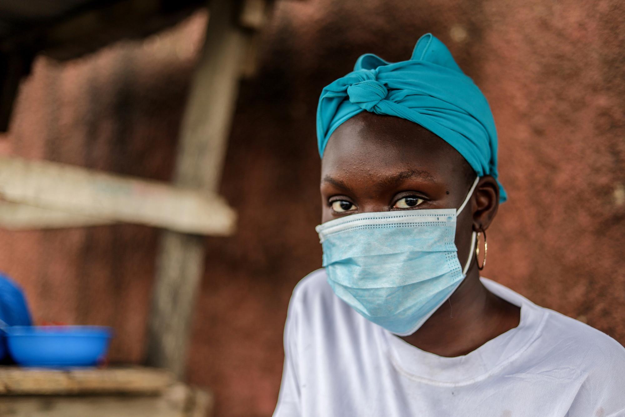 una mujer usa una mascarilla médica frente a un edificio de arcilla.