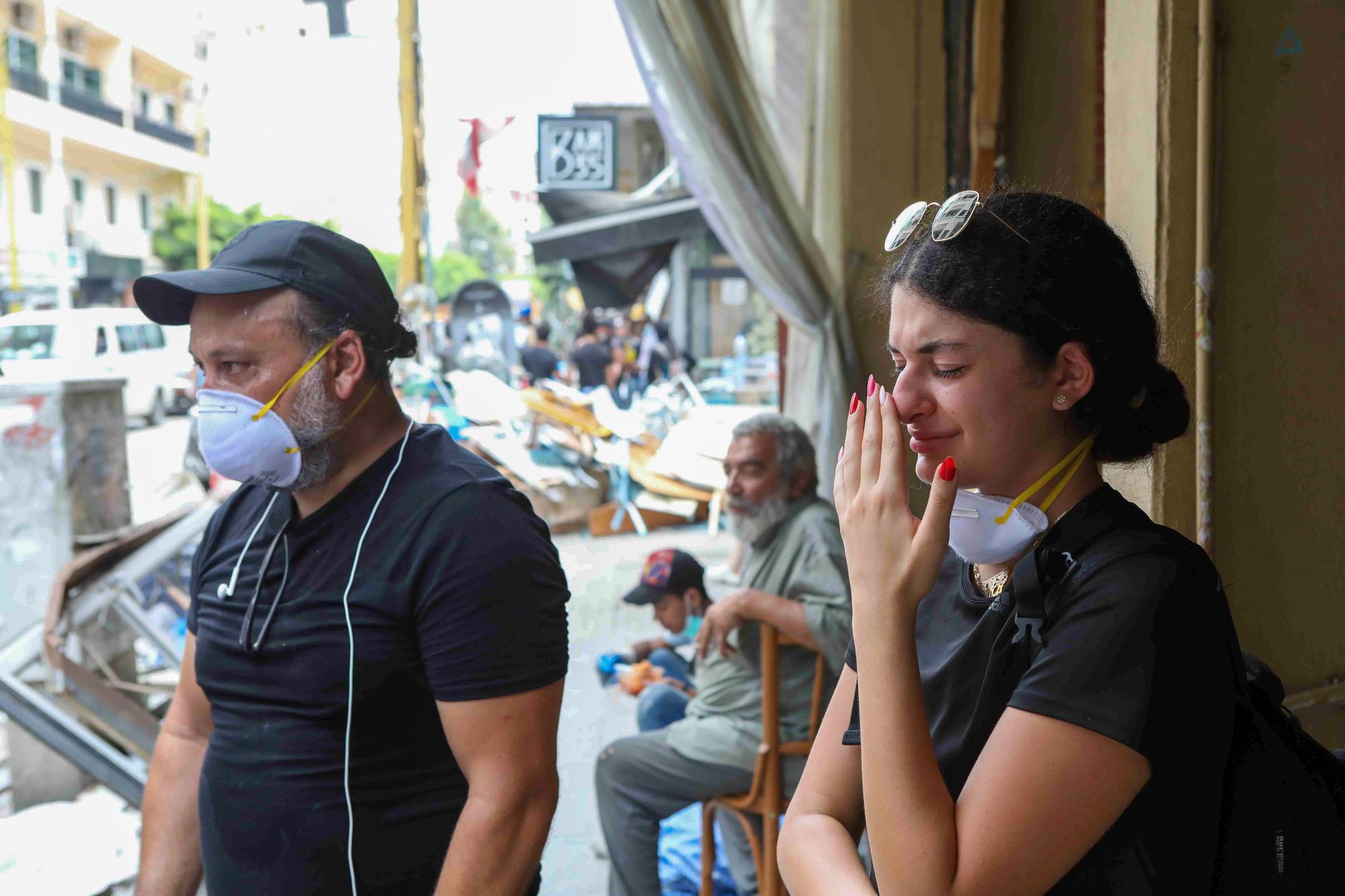 Uma adolescente e um homem choram em frente a uma loja destruída