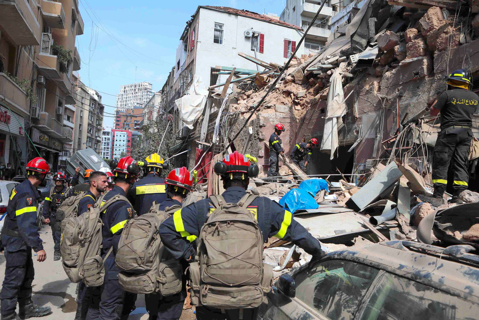 Firemen stand in the rubble of a destroyed city block.