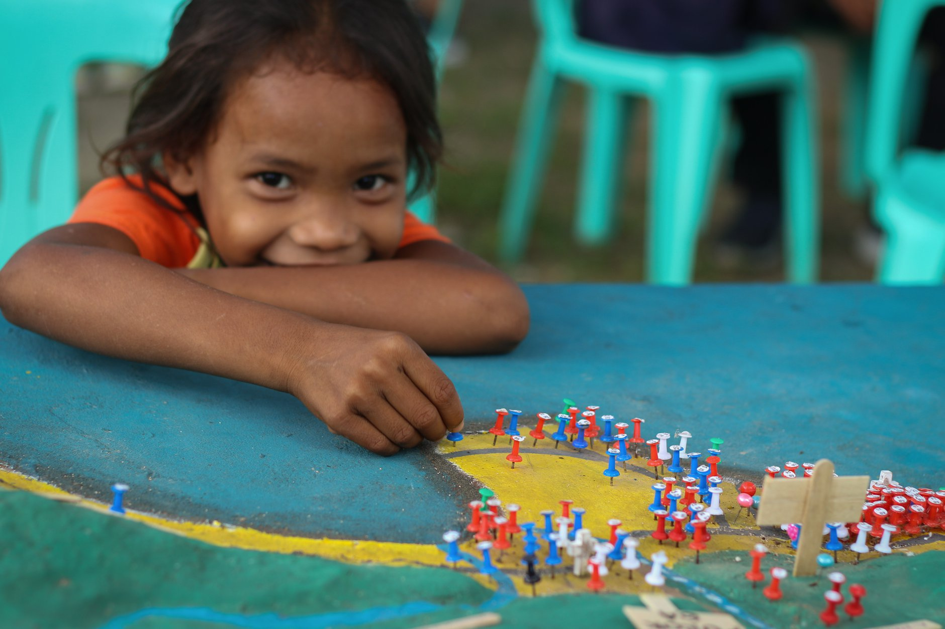 A girl smiles while looking at a map on a table
