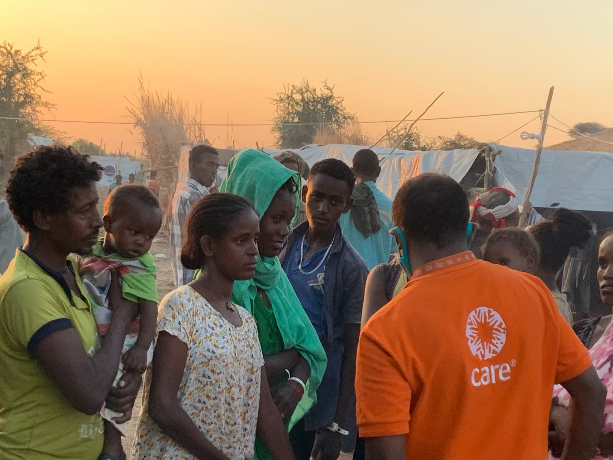 A group of people in a refugee camp speak to a CARE worker in front of tents.