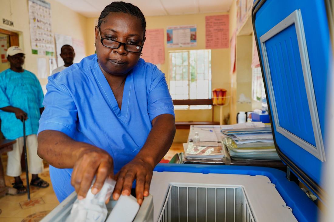 Uma mulher negra vestindo jaleco azul usa uma vacina COVID-19.