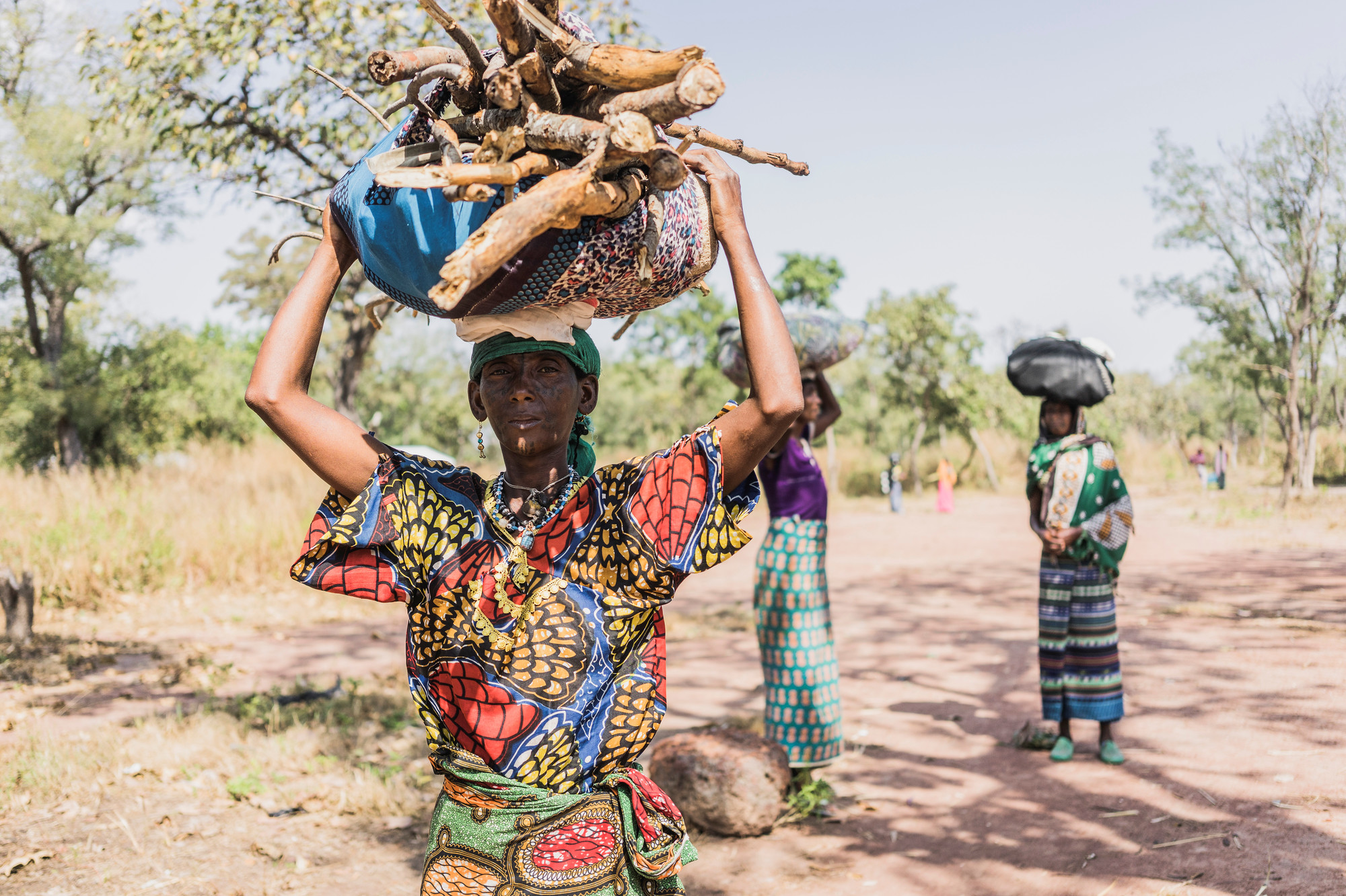 A wan standing outside carries a bundle of firewood on her head.
