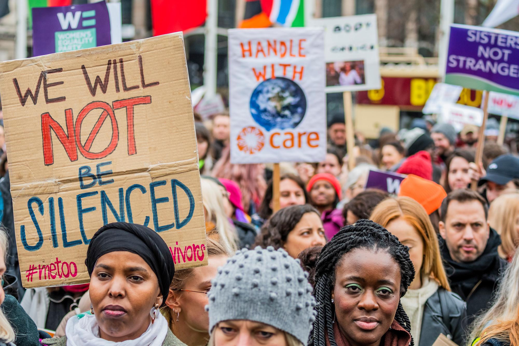 Pessoas marcham nas ruas segurando cartazes.