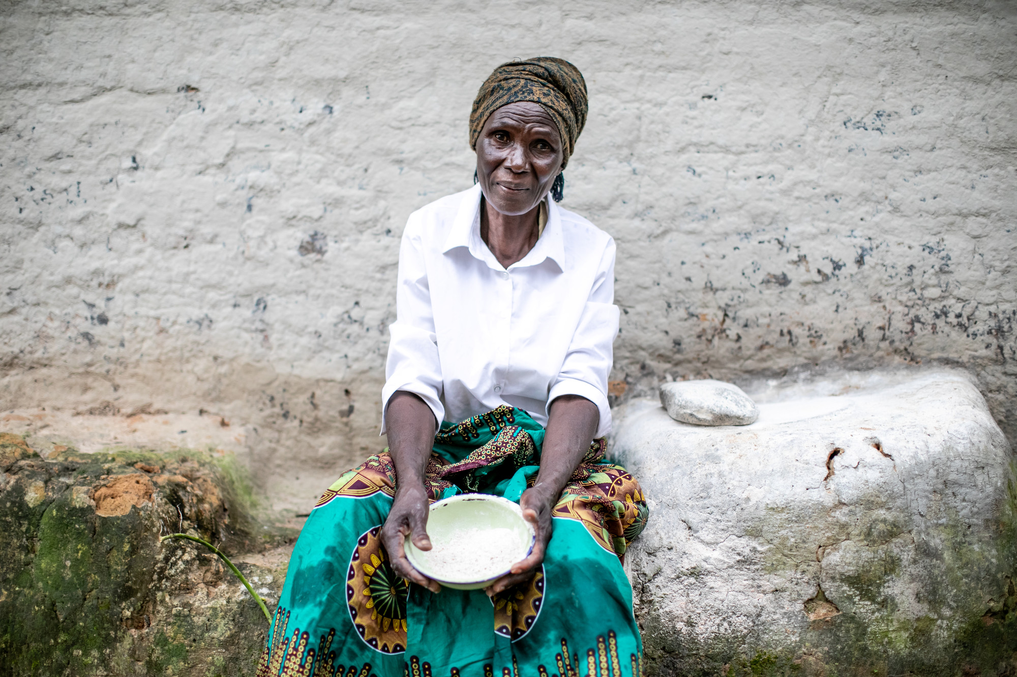 A woman sits outside with a bowl in her hands.