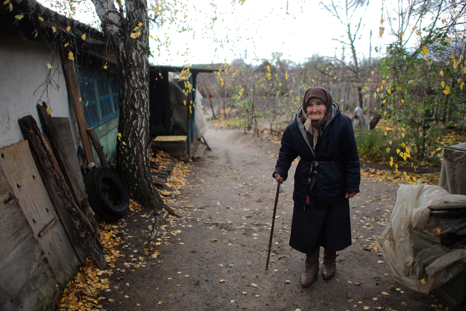 an elderly women walks on the street while holding a cane.