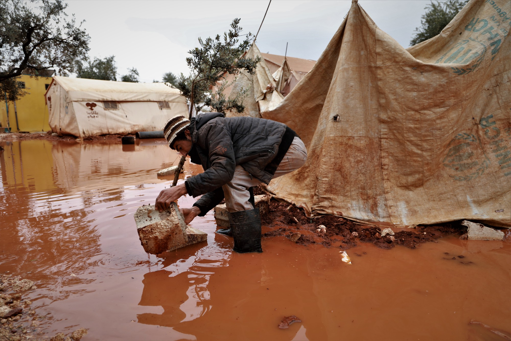 A man bends down outside of a flooded tent in a camp.