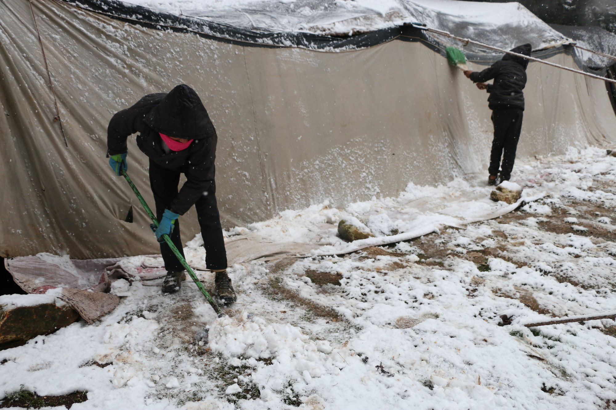 Two children shovel snow outside a tent in a camp.