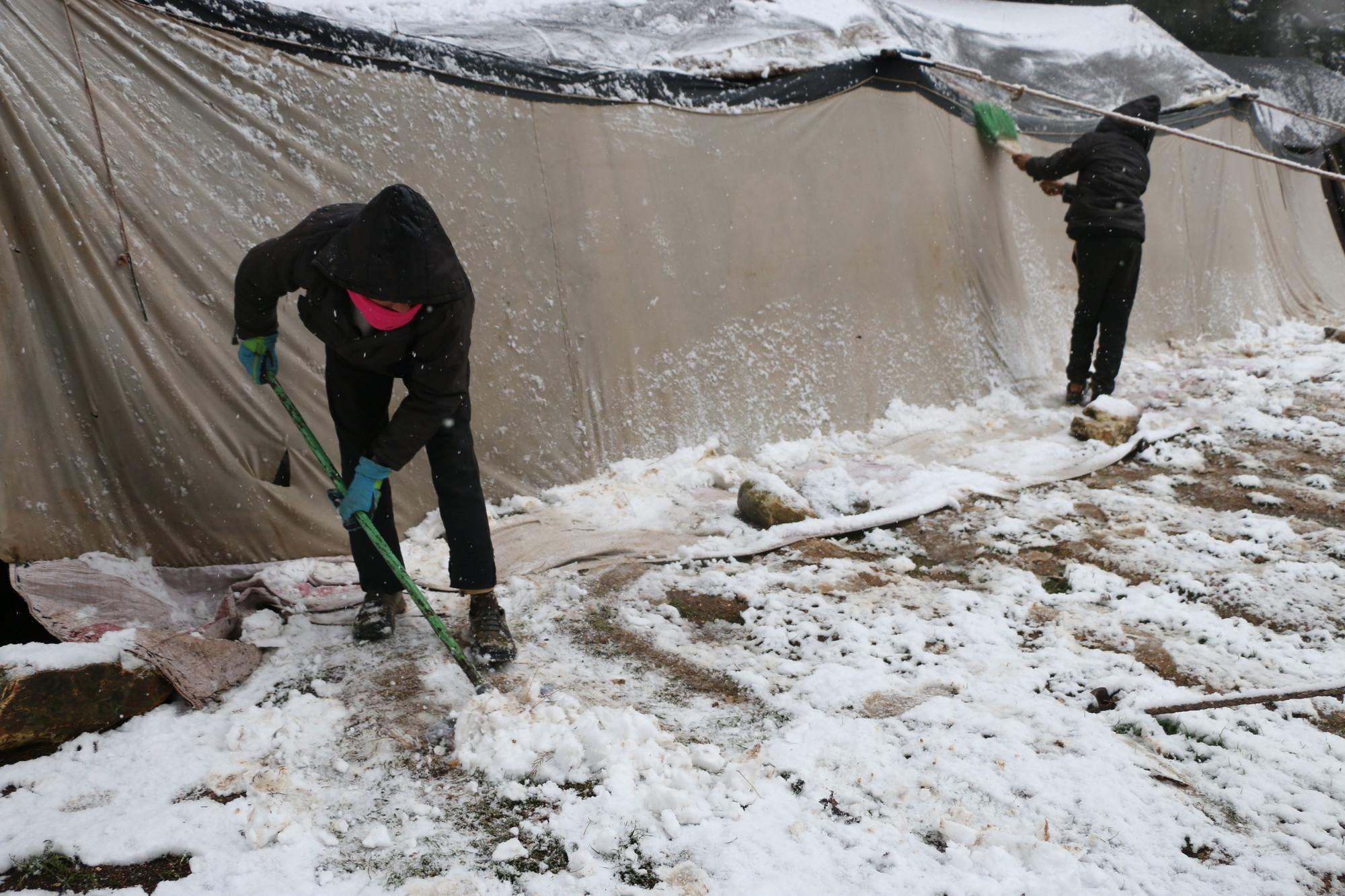 Duas crianças limpam a neve do lado de fora de uma barraca em um acampamento.