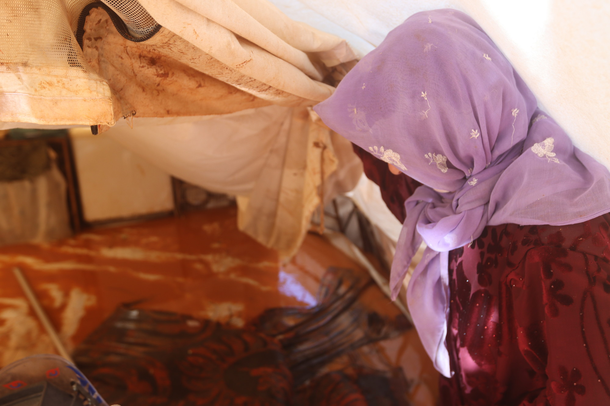 A woman stands inside a flooded tent.