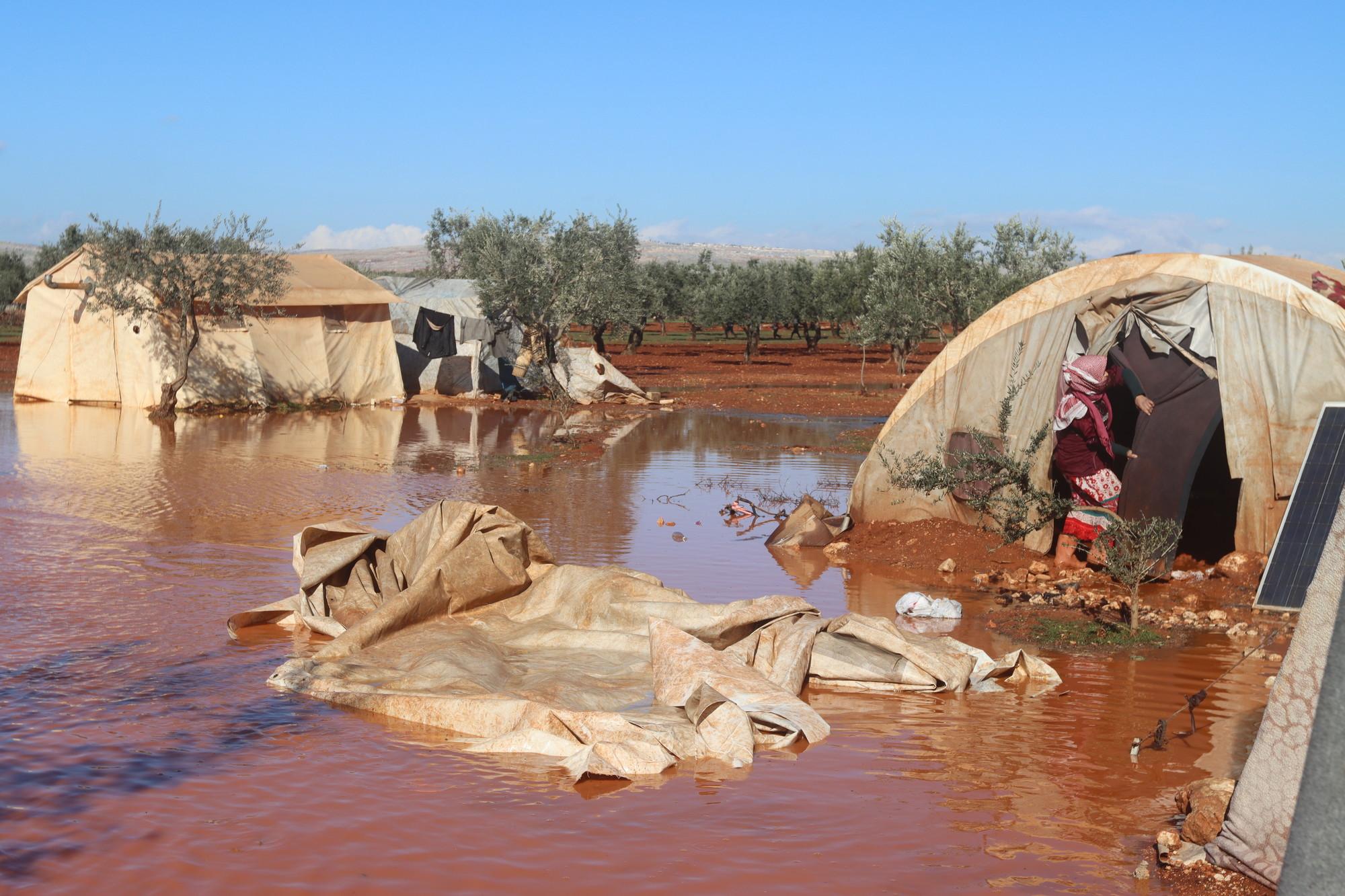Uma mulher entra em uma barraca em um acampamento inundado por água lamacenta na altura dos joelhos.