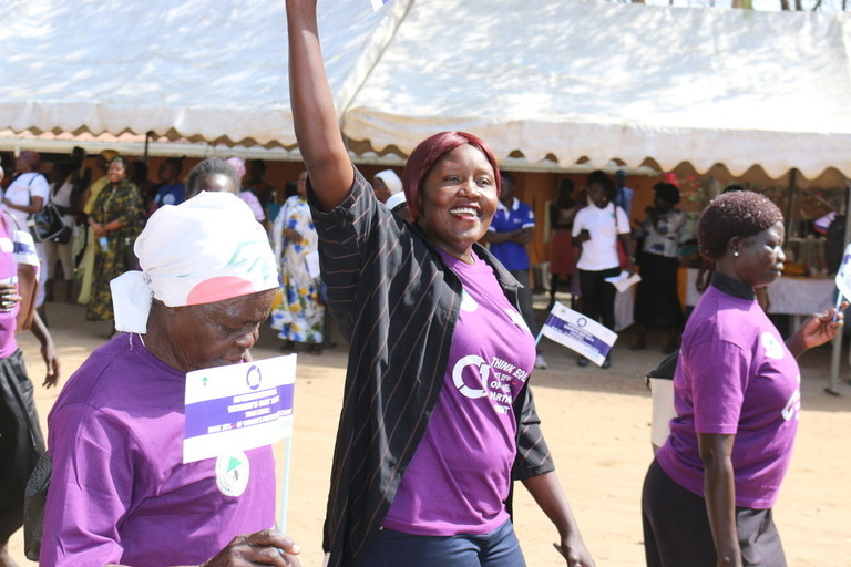 A woman wearing a purple shirt smiles and raises her right arm. She is walking with three other women, all wearing matching purple shirts.