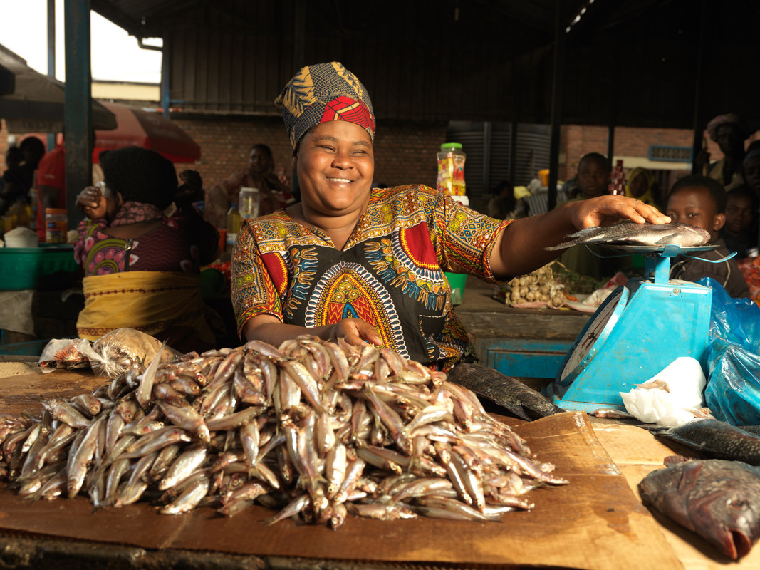 A woman wearing a patterned shirt and hat smiles at a table stacked with fish. She smiles and rests her hand on the table.