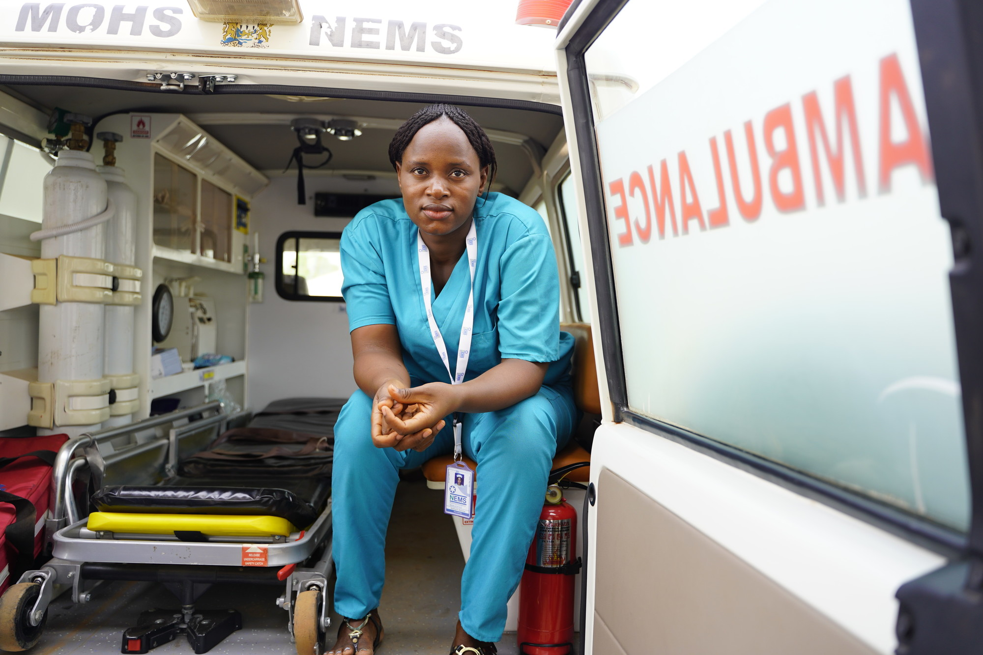 A woman medical professional sits inside the back of an ambulance with the rear door open.