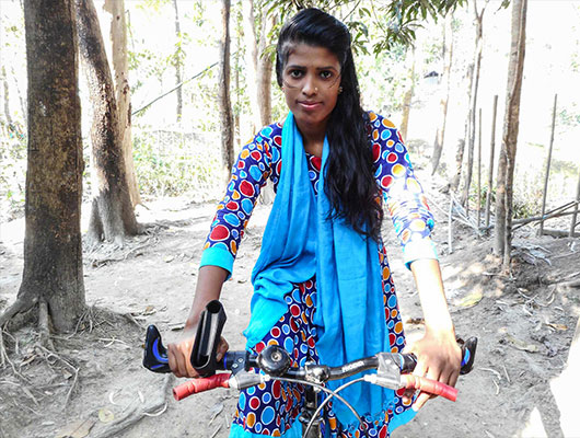A lady wearing a colorful a dress and a blue scarf is riding a bike.