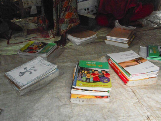 Seven piles of books are on a white tarpaulin.