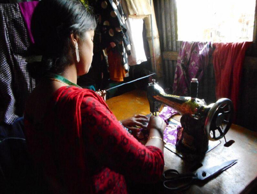 A woman in red clothing is sewing a piece of cloth.