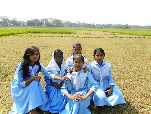 Five young girls in their white and blue school uniform.