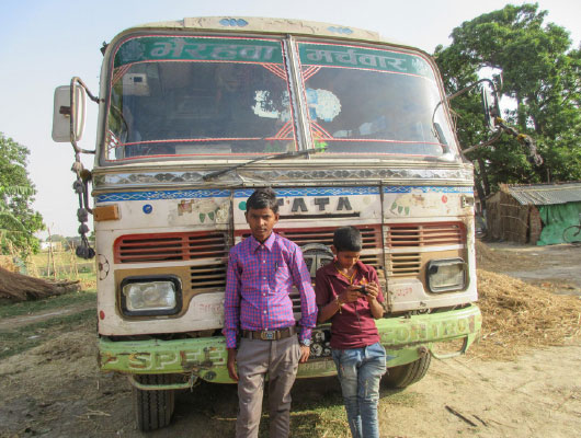 Two young boys stand in front of a van.