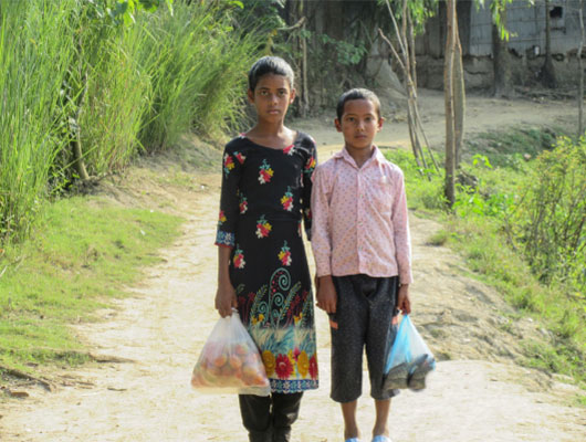 Two young children stand next to each other on a dirt path. They are both carrying bags of groceries.
