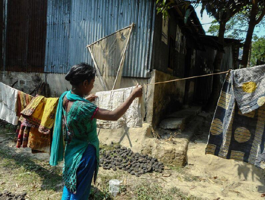 A lady in blue clothing is drying a piece of cloth outside.