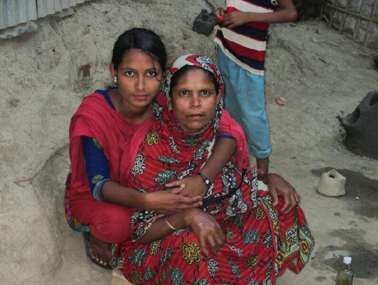 A young lady wearing a pink scarf holds her mother who wears a red piece of cloth.