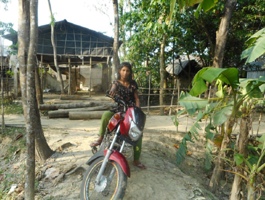 A girl sits on a red motorbike.