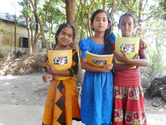 Three young girls wearing boldly colored dresses stand together while holding yellow schoolbooks.