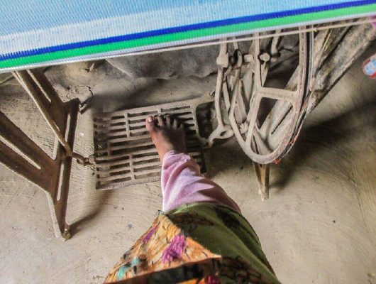 A foot of a woman wearing a pink and green cloth is on the pedal of a sewing machine.