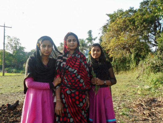 A woman wearing a piece of cloth with red and black stripes stands in the middle of two young girls who are wearing pink dresses and black scarfs.