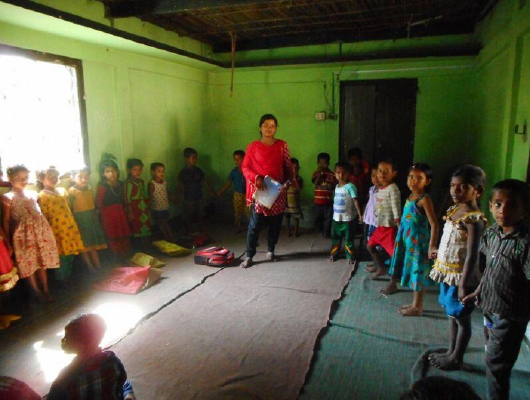 A lady in red clothing stands in the middle of young children while holding a book.