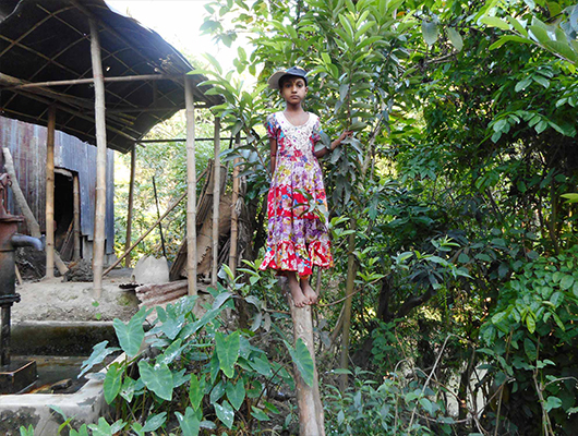 A young girl in a red dress standing on a tree.