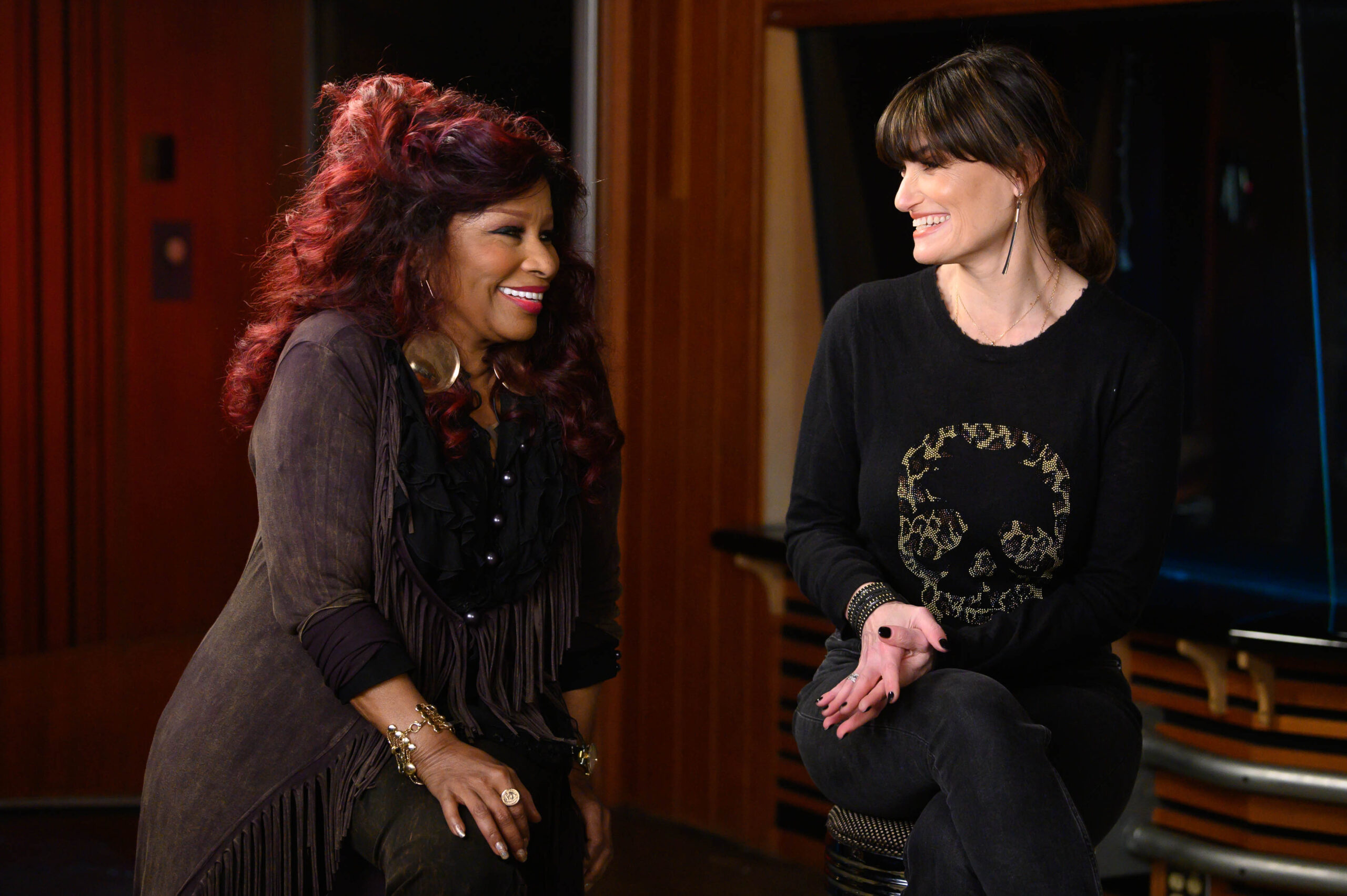 Chaka Khan and Idina Menzel smile widely as they sit next to each other on stools in a recording booth.