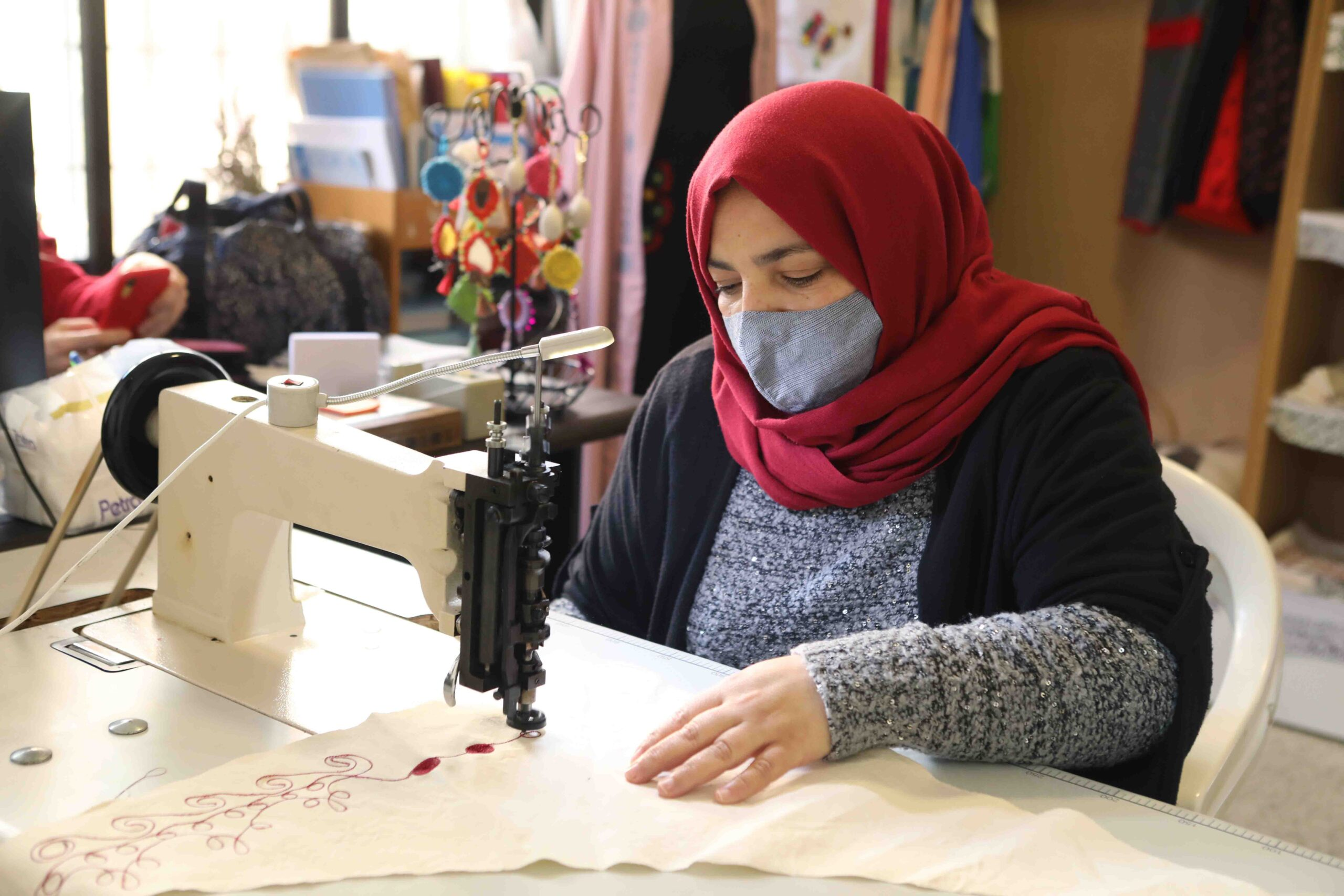 A woman in a face mask uses a sewing machine